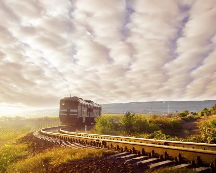 Яркий растровый клипарт с изображением поезда на железной дороге на фоне красивого пейзажа.