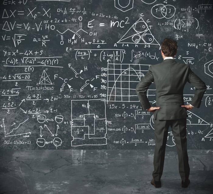 Стоковая фотография с мужчиной в деловом костюме перед доской с формулами.