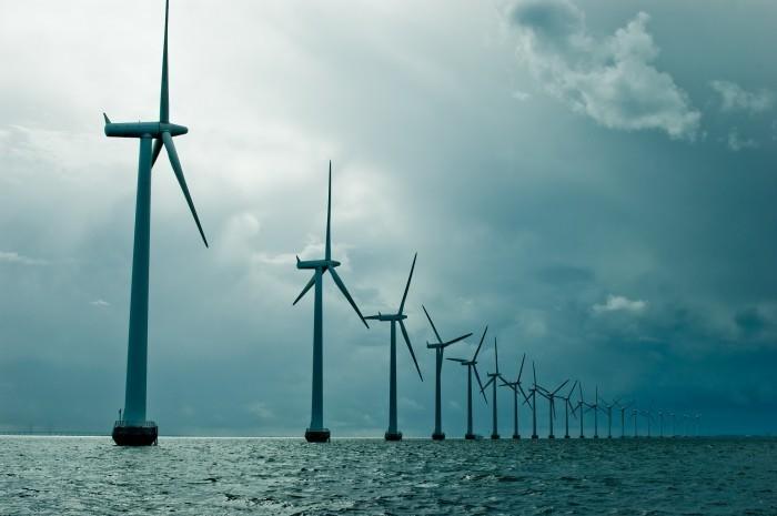 Качественнный растровый клипарт с изображением ветряков стоящих вряд на море.
