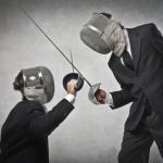 Качественный растровый клипарт из изображением тандем мужчин во деловых костюмах сражающихся сверху шпагах.