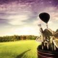 Клюшки для игры в гольф на фоне поля.