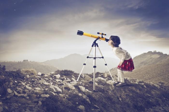 Качественный растовый клипарт с изображением девочки с подзорной трубой на скалистой местности.