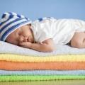 Спящий младенец на цветных полотенцах.