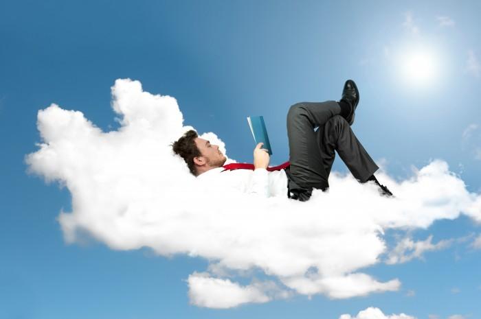Качественный растровый клипарт с мужчиной в деловом костюме на облаке с книгой в руках.