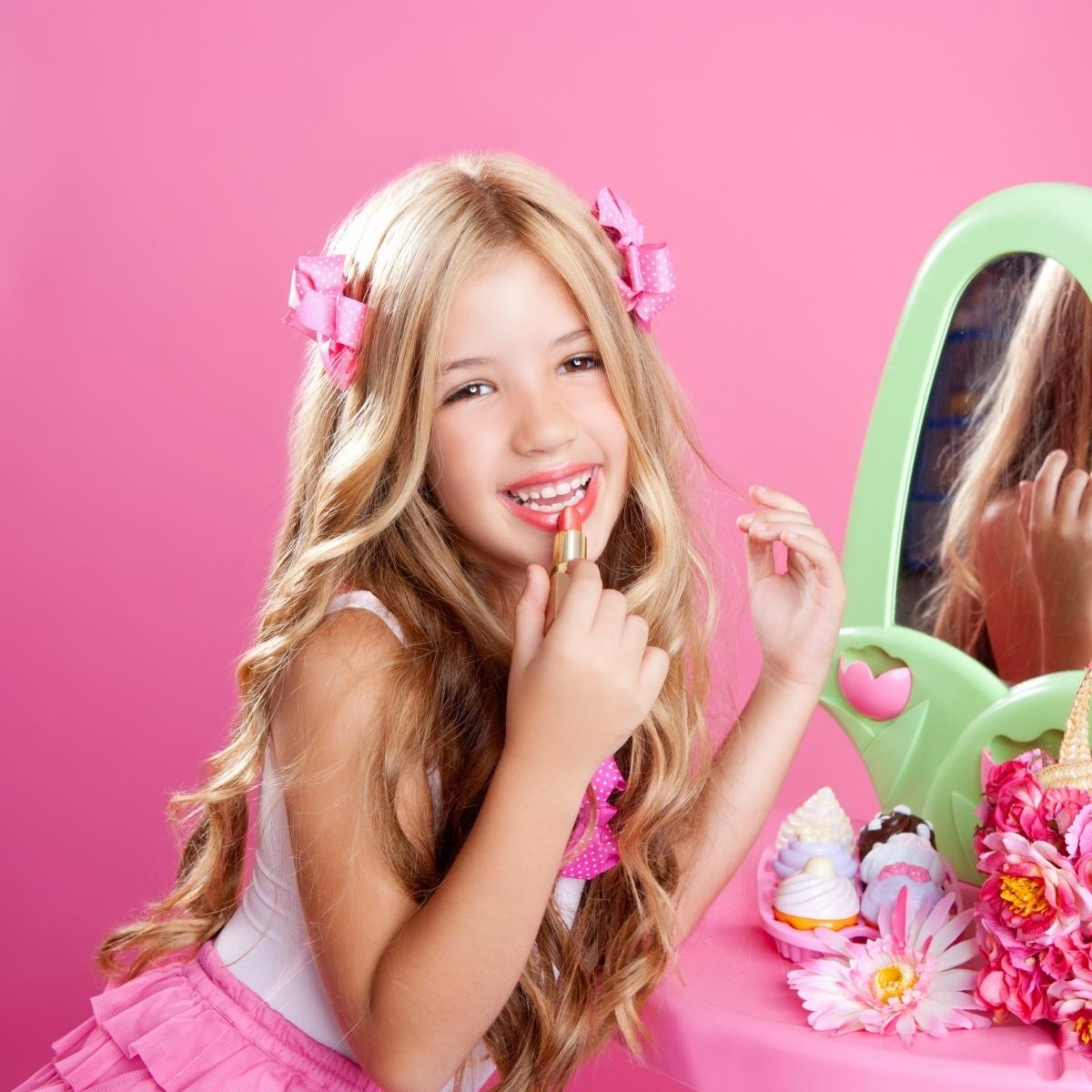 Девочка с помадой перед зеркалом в розовых тонах.