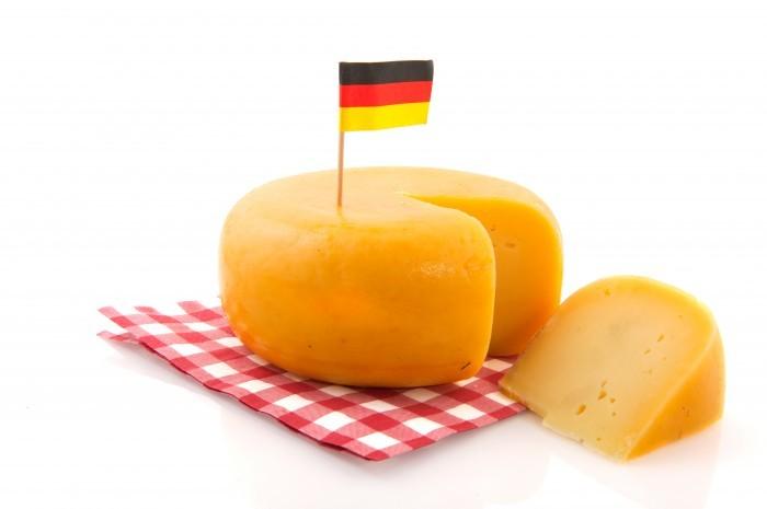 Качественная стоковая фотография с сыром и немецким флажком на белом фоне.