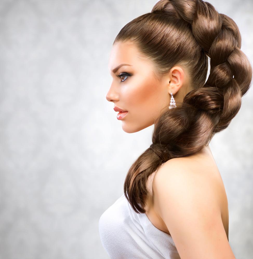 Красивая девушка с заплетенной косой в профиль.