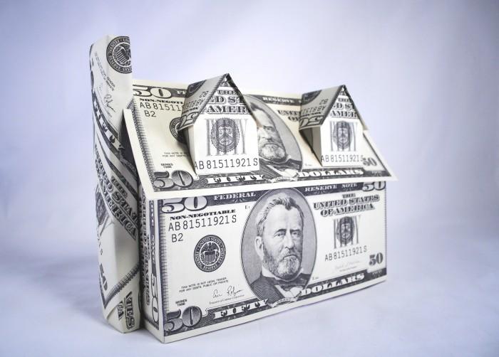 Растровый клипарт с домом из купюр долларов на голубом фоне.