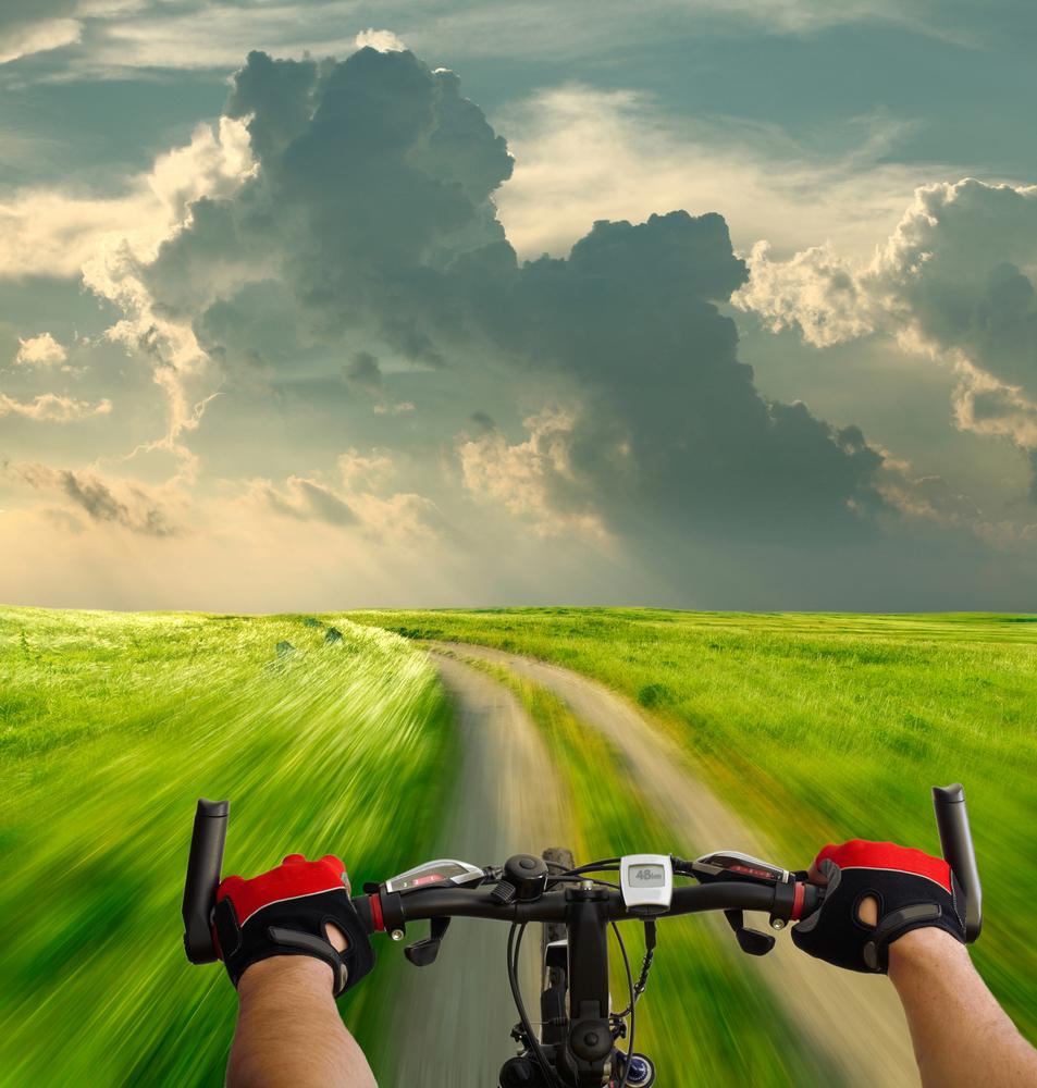 Качественный растовый клипарт с изображением рук велосипедиста в перчатках с видом на дорогу в сельской местности.