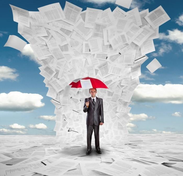 Мужчина с красным зонтом под печатными листами.