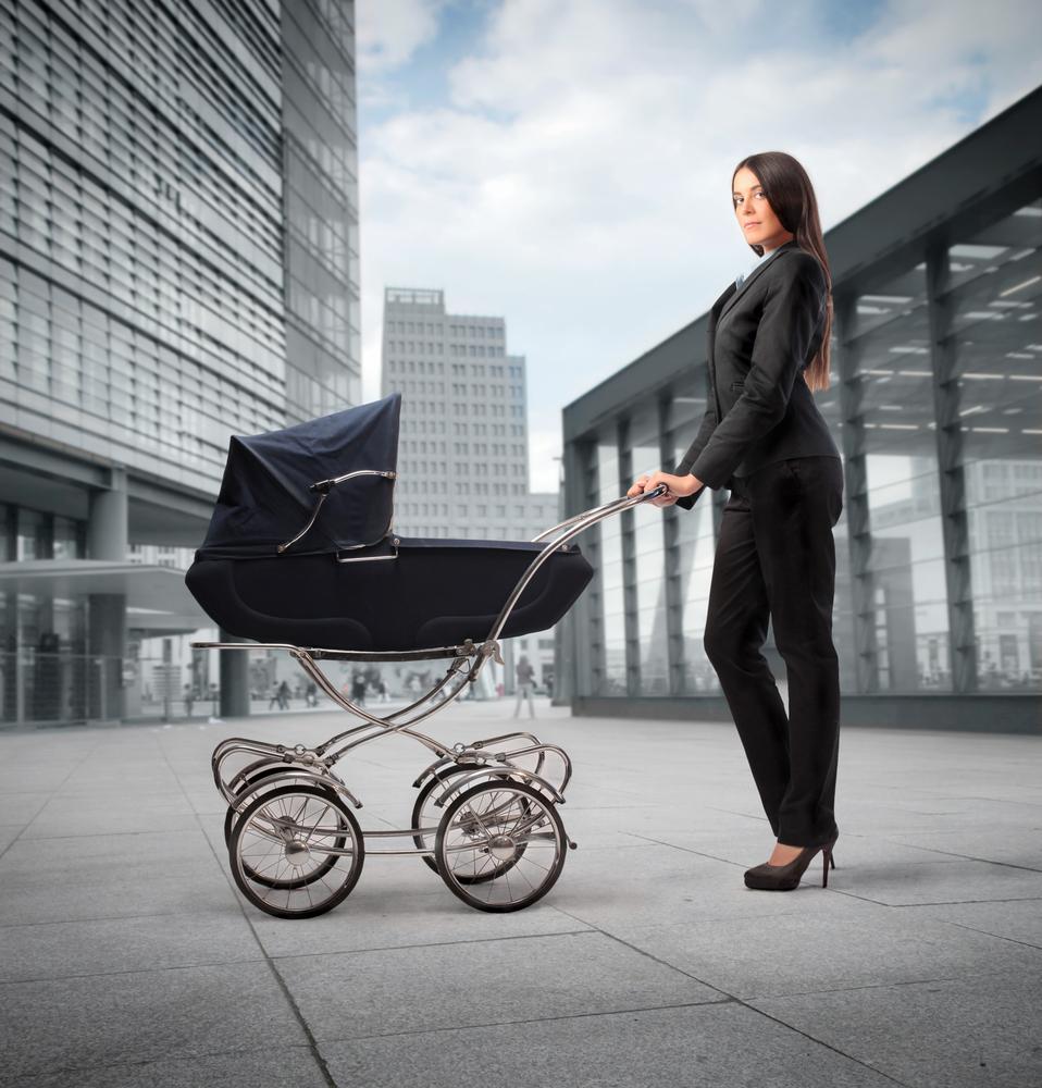 Стоковая фотография с женщиной в деловом костюме с коляской.