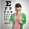 Парень в очках перед таблицей проверяющей зрение - Guy with glasses in front of a table checking eyesight