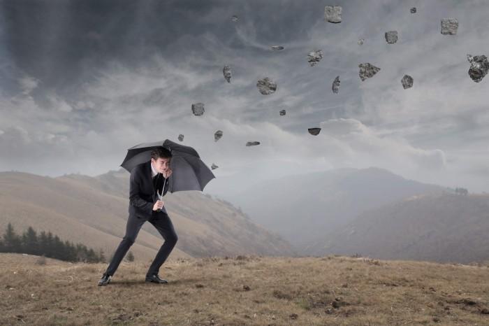 man umbrella stones Мужчина под зонтом под дождем из камней   Мan under an umbrella in the rain of stones