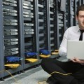 Мужчина с ноутбуком возле серверов - Man with a laptop next to servers