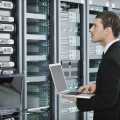 Мужчина с ноутбуком у сервера - Man with a laptop at the server