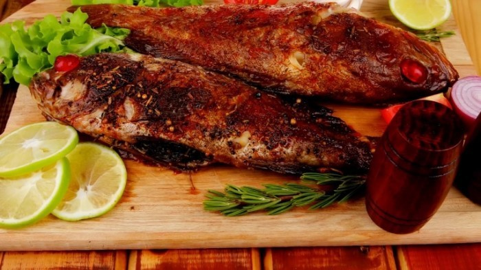 stock footage healthy food two fried sea bass fish served with tomatoes and vegetables on big wooden board over 700x393 Жареная рыба   Fried fish