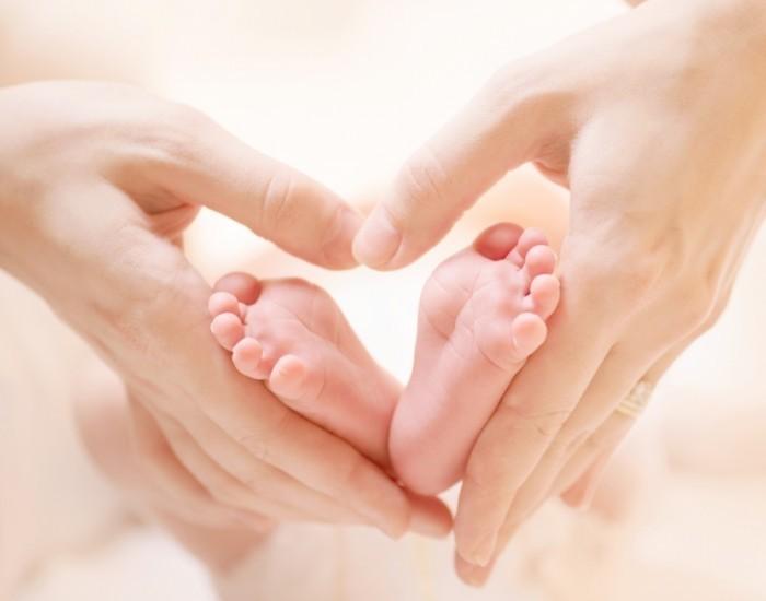 Dollarphotoclub 604744801 700x550 Детские ножки в руках   Childrens feet in the hands of