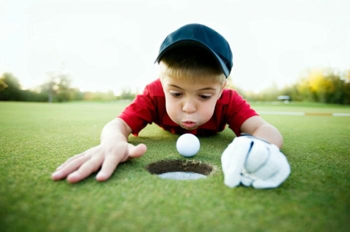 IStockPhotoJrgolferBlowing 700x465 Мальчик с мячом для гольфа   Boy with a golf ball