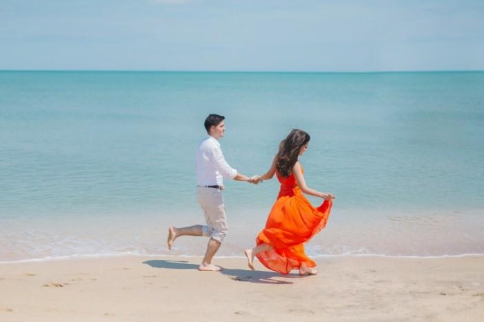 Пара бежит по побережью моря босиком   couple runs along the coast of the sea barefoot