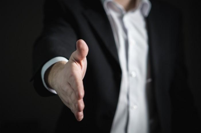 Человек в черном костюме протягивает руку   Man in a black suit holds out his hand