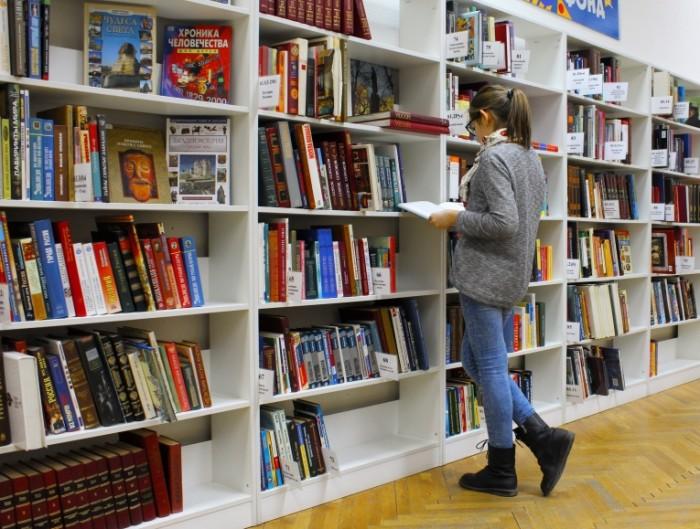 Девушка в книжном магазине выбирает книгу   girl in the bookstore chooses a book