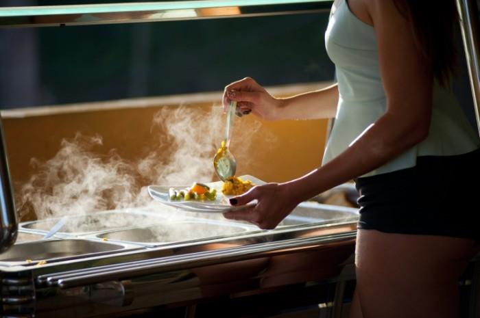 Шведский стол, девушка накладывает еду, пар от пищи   Buffet, girl puts food, steam from food