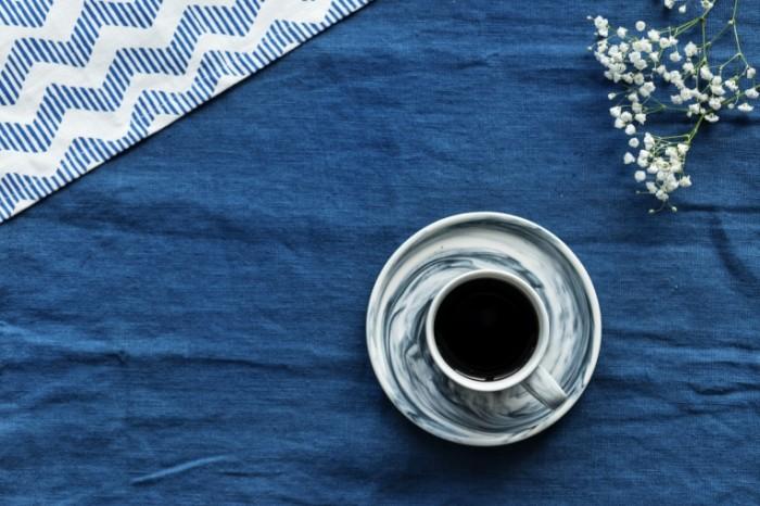 Чашка кофе на синей скатерти   cup of coffee on a blue tablecloth